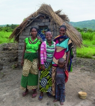 Bawili Hamisi (43) and some of her family by their latrine, Mwandiga 3 Community, Eastern DRC.